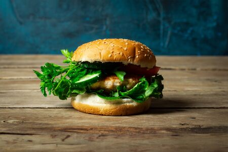Photo pour Fresh home-cooked appetizing tasty burger with chicken on wooden table. - image libre de droit