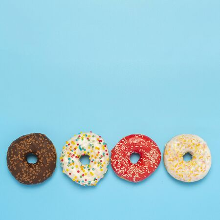 Photo for Tasty donuts of different types on a blue background. Concept of sweets, bakery, pastries. Square. Flat lay, top view. - Royalty Free Image