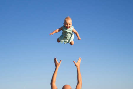 Photo pour Man throws baby up against the blue sky. Concept game with children, happy family. - image libre de droit