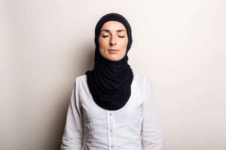 Photo pour Young woman with closed eyes in white shirt and hijab on light background. - image libre de droit