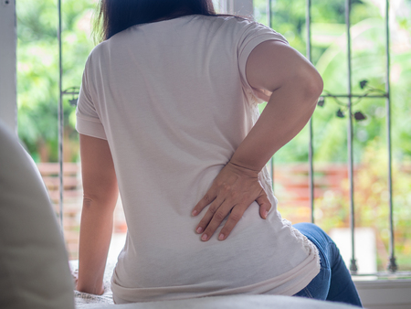 Foto de Young woman feeling pain in her back sitting on the sofa at home. Healthcare and medical concept. - Imagen libre de derechos