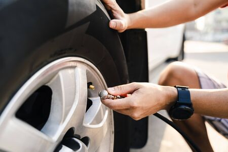 Photo pour Close up of asian man inflating tire in the gas station. - image libre de droit
