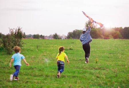 Photo for two children a boy in a blue T-shirt and a girl in yellow run for a kite into the distance. - Royalty Free Image