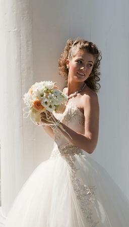 Foto de The bride with a bouquet. The bride in a wedding dress with a bouquet on the white. - Imagen libre de derechos