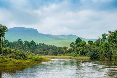 Photo pour River in the Jungle. Small river in jungle. Under the cloudy sky through hills and mountains the small river proceeds on jungle. Congo. Africa - image libre de droit
