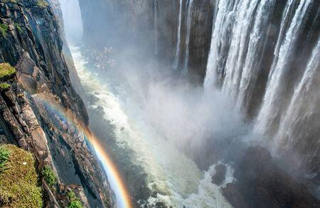 Rainbow Over Victoria Falls On Zambezi River Border Of
