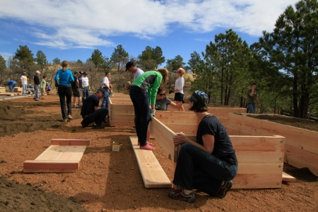 Raised garden beds are being prepared by team of people.