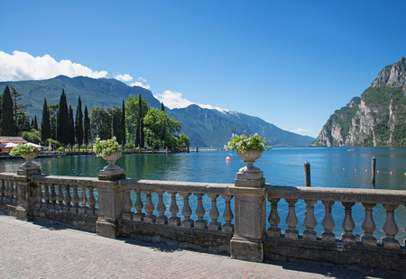 Photo pour lakeside promenade riva with flower pots and lake view garda lake italy - image libre de droit