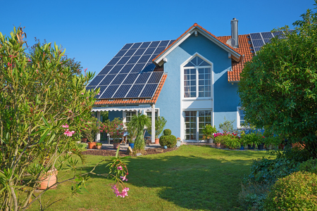 Photo for backyard garden of a beautiful family home with solar panels on the roof and idyllic garden with mediterranean plants - Royalty Free Image