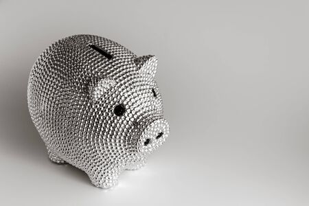 Silver metal piggy bank with black eyes on a gray background in the soft daylight.