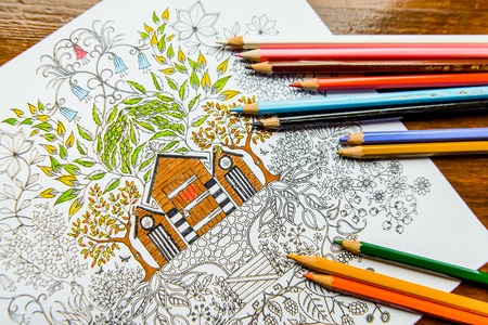 Anti-stress coloring book in the drawing process. Woman paints the razukrashki on the table are colored pencils, and tea, coffee