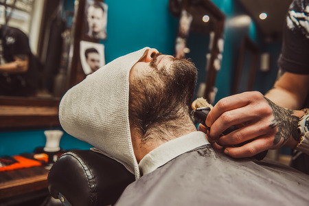 Cropped closeup of a young man having his beard shaped in a barbershop