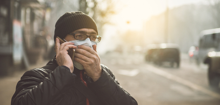 Photo pour A man wearing a mask on the street. Protection against virus and grip - image libre de droit