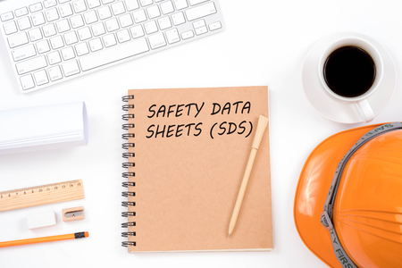 Photo pour Concept SAFETY DATA SHEETS (SDS). Top viwe of modern workplace with safety helmet, office supplies, a cup of coffee and keyboard on white background. Safety & Health. - image libre de droit