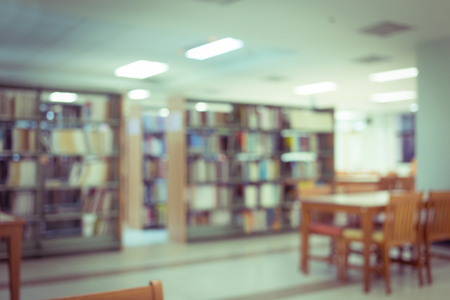 Foto de bookshelf and table desk in library, education abstract blur defocused background - Imagen libre de derechos