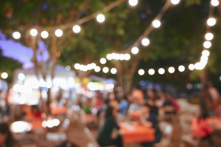 Photo pour people crowd in night party festival of outdoor garden with light bulb hanging decoration, image blur used for celebration background - image libre de droit