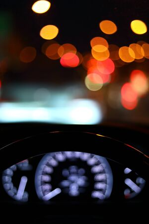 Photo for black steering wheel inside car drive in night city street - Royalty Free Image