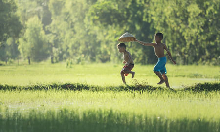 Photo pour Action two children running on the berms, ditches in fields. playfully The life of children a farmer in Thailand. - image libre de droit