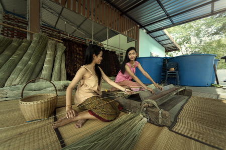 Asia, Thailand Girls are Textiles with the papyrus the mat.
