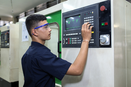 Photo for Man programming CNC machine - Royalty Free Image