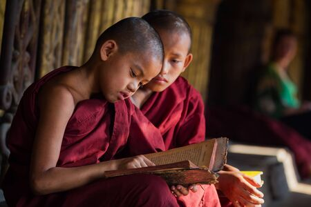Two novice Myanmar Reading a book in the cathedrals
