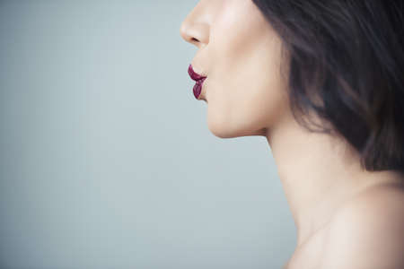 Photo for Makeup artist applies red lipstick . Beautiful woman face. Hand of make-up master, painting lips of young beauty model girl . Make up in process - Royalty Free Image