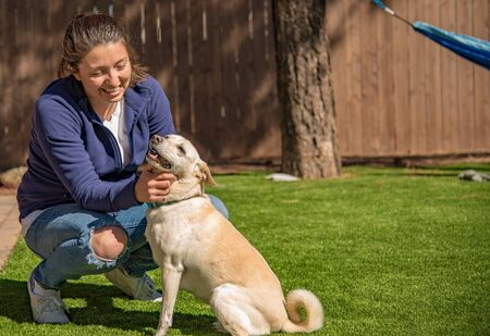 Pretty girl petting a happy white dog with a curly tail in a backyard with a hammock in the background.