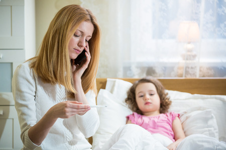 Mother measuring temperature of her ill kid. Sick child with high fever laying in bed and mother holding thermometer. Mother with cell phone calling to doctor
