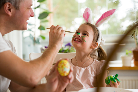 Photo for A father and daughter celebrating Easter, painting eggs with brush. Happy family smiling and laughing, drawing on face. Cute little girl in bunny ears preparing the holiday. - Royalty Free Image