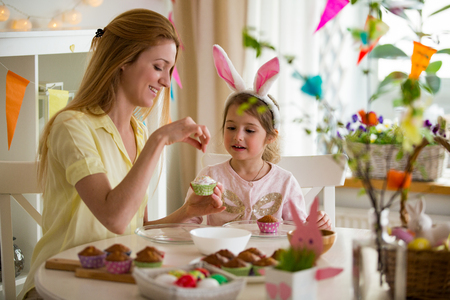 Photo for Mother and daughter celebrating Easter, cooking cupcakes, covering with glaze. Happy family holiday. Cute little girl in bunny ears. - Royalty Free Image