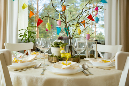 Foto de Beautiful served round table with decorations in dining room. Little yellow bunny, willow branches decorated with colorful Easter eggs. Spring holiday setting - Imagen libre de derechos