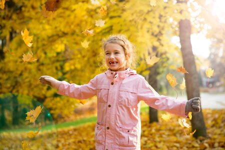 Photo for Cute little girl with missing teeth playing with yellow fallen leaves in autumn forest. Happy child laughing and smiling. Sunny autumn forest, sun beam. - Royalty Free Image