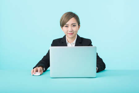 Photo pour A young woman in a black suit smiling as she operates her laptop with a green desk. - image libre de droit