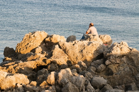 Bold fishmen is sitting on the rocks on sunset