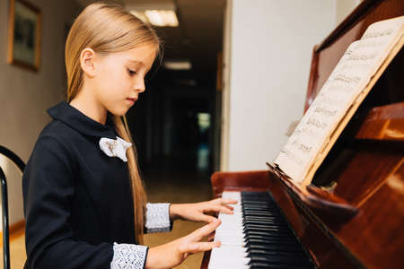Photo pour Little girl in a black dress learns to play the piano. The child plays a musical instrument. - image libre de droit
