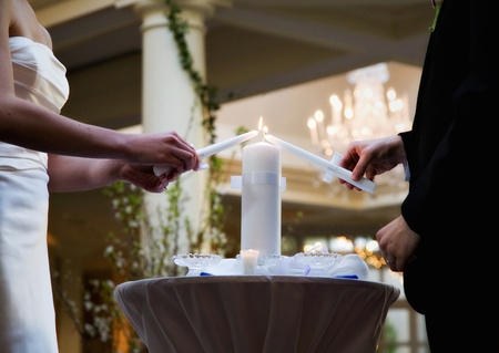 Bride and Groom lighting a white unity candle at their wedding
