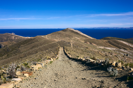 Path leading on ridge on Isla del Sol, Lake Titicaca, Bolivia. Isla del Sol (Island of the Sun) is a popular travel destination.