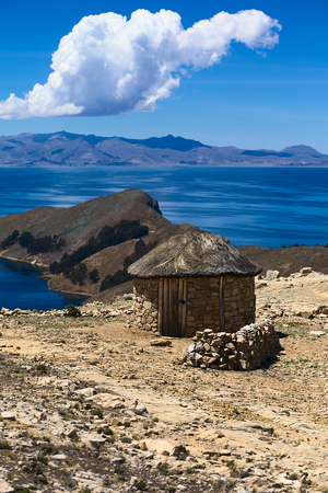 Small stone hut with thatched roof on Isla del Sol (Island of the Sun) in Lake Titicaca, Bolivia. The island is a popular tourist destination.