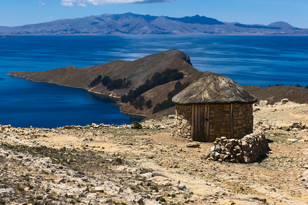 Small round stone hut with thatched roof on Isla del Sol (Island of the Sun) in Lake Titicaca, Bolivia. The island is a popular tourist destination.