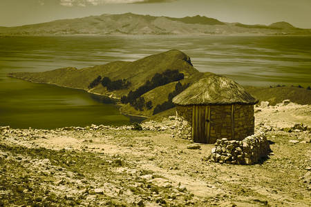 Small round stone hut with thatched roof on Isla del Sol (Island of the Sun) in Lake Titicaca, Bolivia. The island is a popular tourist destination. (Digitally Altered: Split Toned Image)