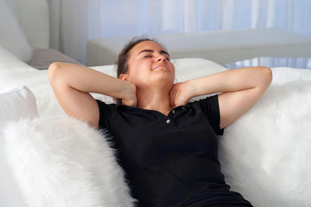 Tired neck. Young woman suffering from neck pain at home on couch. A woman\'s sense of fatigue, exhausted, stressed. A girl massages her painful neck with her hands. The concept of body and health.