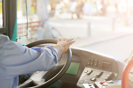 Photo pour Hands of driver in a modern bus by driving.Concept - close-up of bus driver steering wheel and driving passenger bus. Toning - image libre de droit