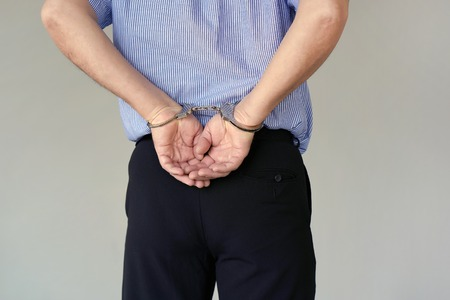 Photo pour Close-up. Arrested elderly man handcuffed hands at the back isolated on gray background. Prisoner or arrested terrorist, close-up of hands in handcuffs. Close-up view - image libre de droit