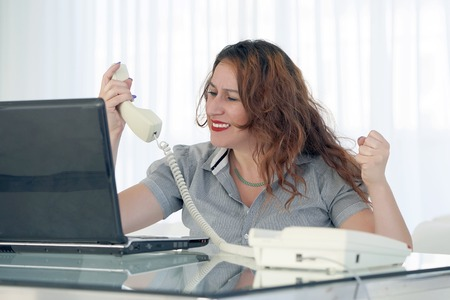Photo pour Close-up of an office worker swears with the client by phone. A woman is shouting into the phone's phone. Funny facial expressions, emotions, reaction of perception, stress, gilding, nerves. - image libre de droit