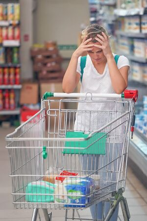 Foto für Upset woman in a supermarket with an empty shopping trolley. Crises, rising prices for goods and products. Woman shopping at the supermarket. - Lizenzfreies Bild