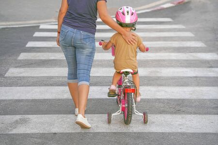Photo for Mother goes pedestrian crossing with daughter on bicycle. A woman with child crossing the road in the city. Back view. - Royalty Free Image