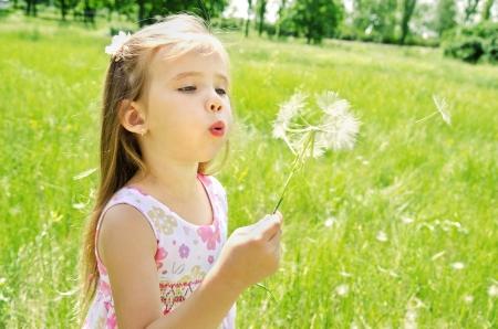 Beautiful little girl blowing dandelion on green meadow