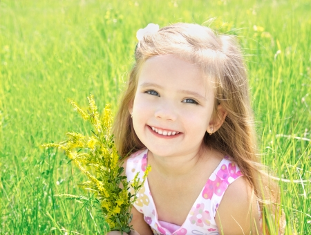 Cute little girl on the meadow with flowers in summer dayの写真素材