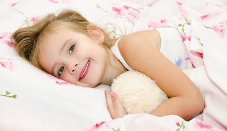 Cute smiling little girl waked up in her bed with toy