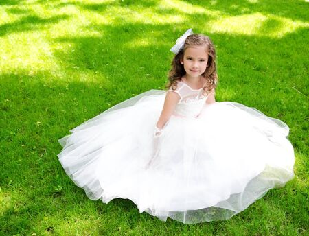 Adorable smiling little girl in princess dress sitting on grass outdoor